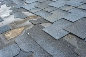 close up of damaged roof shingles; roofing warranties