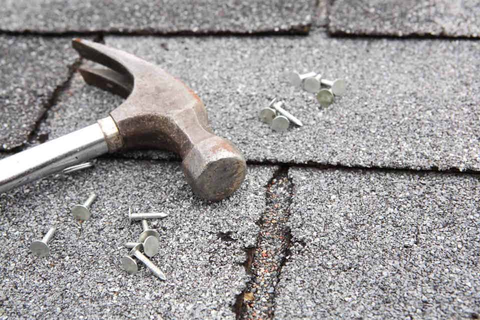 close up view of hammer and nails laying on roof shingles; roofing scams