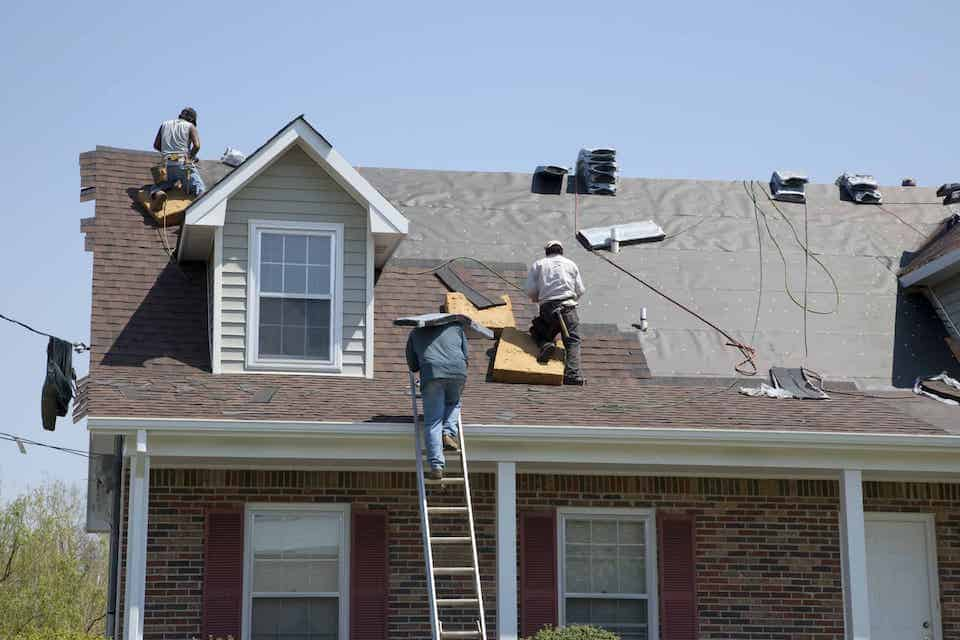 Roofers replacing damaged shingles after storm with very high winds came through over night; roofing scams