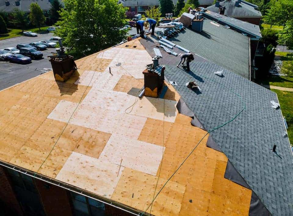 aerial view of contractors repairing home roof; roofing materials