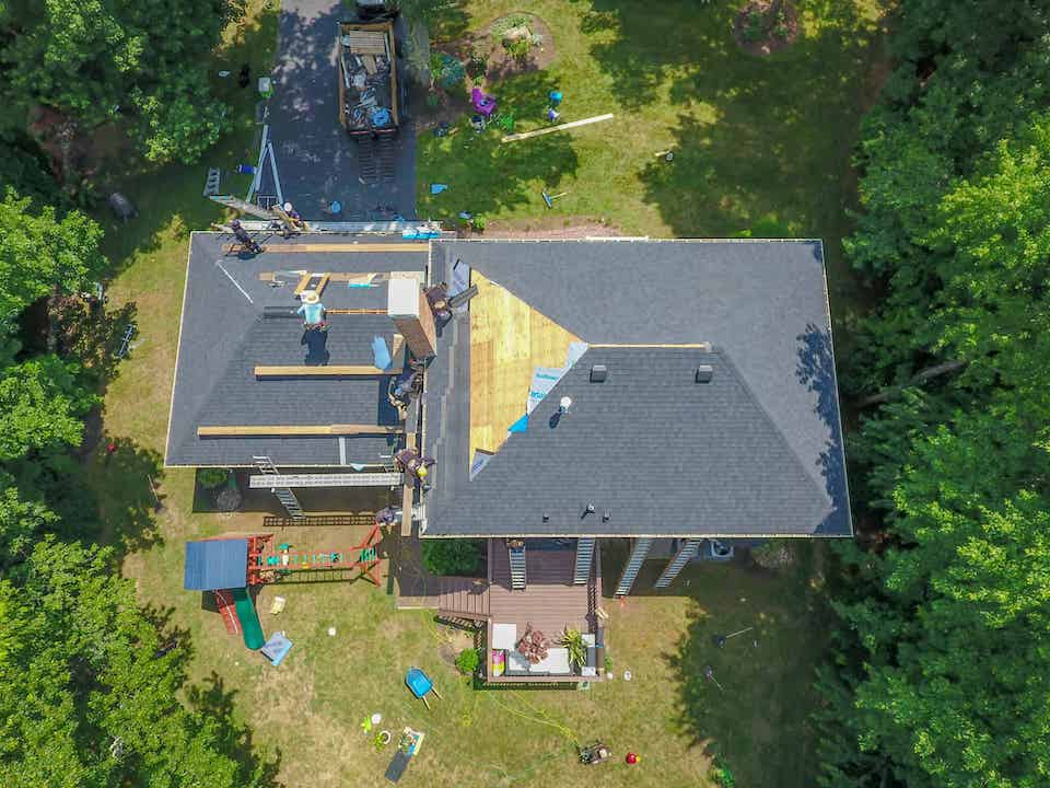 aerial view of home having roof repaired; best roofing materials