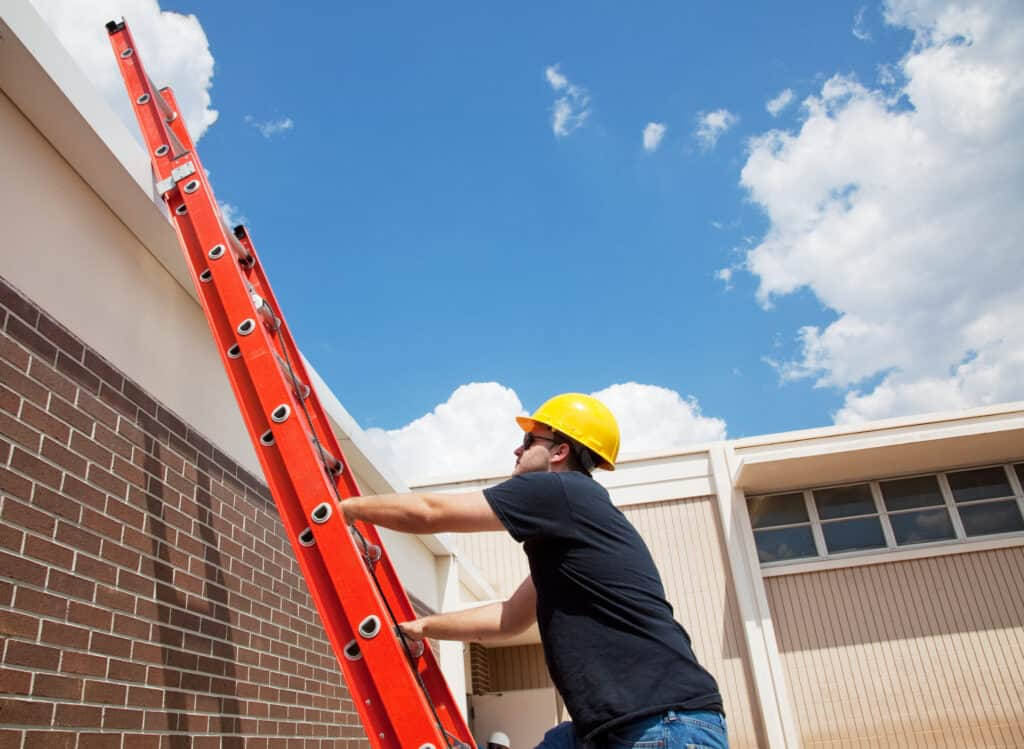 man climbing up his roofing ladder