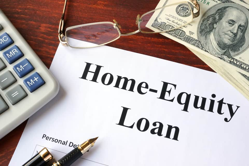 desktop with a paper headline reading home equity loan; roof financing options