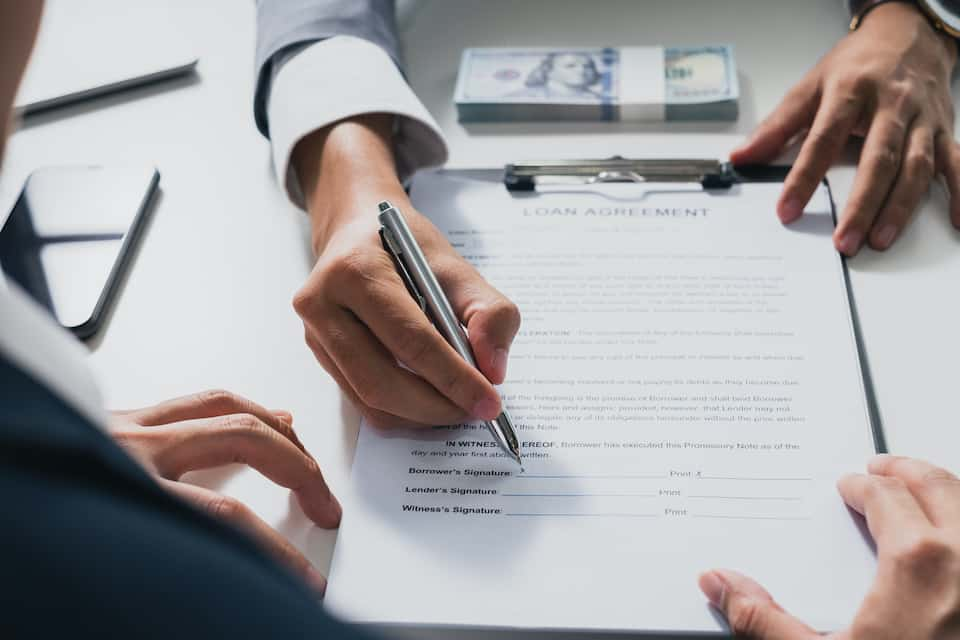 Businessman sign on money loan agreement contract to banker, loan and credit financial lease concept; roof financing options