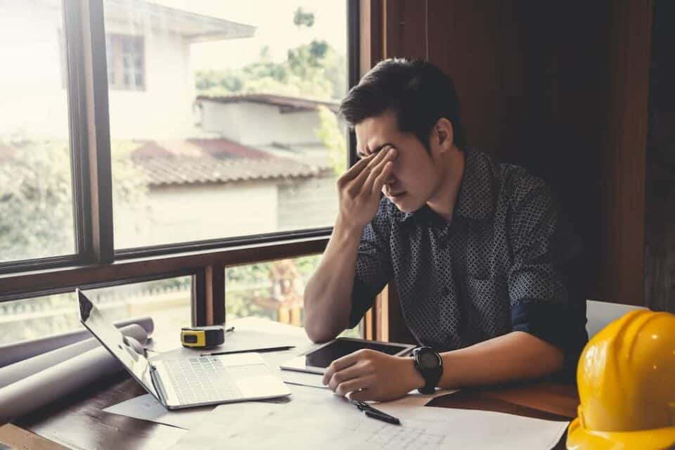Man, that's clearly frustrated sitting at work desk in front of an open laptop;  8 simple ways to generate effective roofing leads